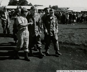 Congressman Arch A. Moore, Jr. talking to an unidentified solider while walking. Another unidentified man is walking with them. In the background there is a large group of Vietnamese people.