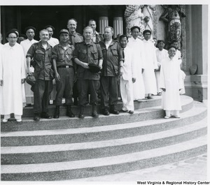 Congressman Arch A. Moore, Jr. standing on the steps of the Cao Dai Temple with an unidentified group of men.