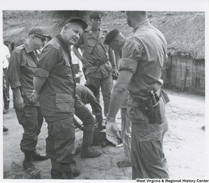 Congressman Arch A. Moore, Jr. talking to an unidentified Army solider. Other soldiers are standing behind and beside him.