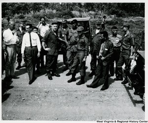 Congressman Arch A. Moore, Jr. standing with a group of unidentified men, some of whom are soldiers in the U.S. Army, in Vietnam.