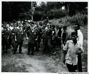 Congressman Arch A. Moore, Jr. standing with a large group of people in Kon Hojao Montagnard village, near Dac To, in the Kon Tum Province of Vietnam.