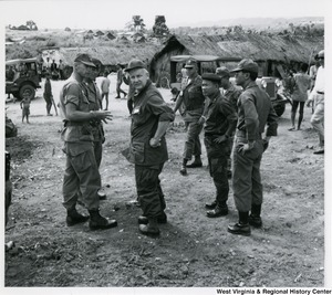 Congressman Arch A. Moore, Jr. looking at something behind him. He is talking with soldiers in Vietnam.