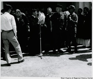 Congressman Arch A. Moore, Jr. talking to an unidentified man who is standing by a microphone. They are surrounded by a group of men at the Cau Ca resettlement in Vietnam.