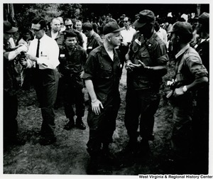 Congressman Arch A. Moore, Jr. having a conversation with two soldiers in Vietnam. There is a large group of people behind them.