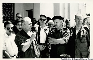 Congressman Arch A. Moore, Jr. watching an unidentified man give a speech in Vietnam. Other people are standing with Moore watching.