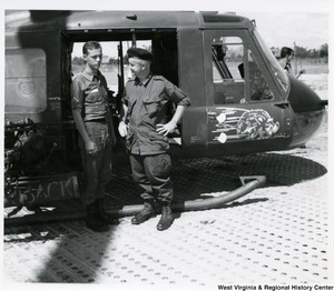 Congressman Arch A. Moore, Jr. standing beside a helicopter talking to PFC James Goff (Shinnston, W.Va.), who was on the gun chopper escort crew.