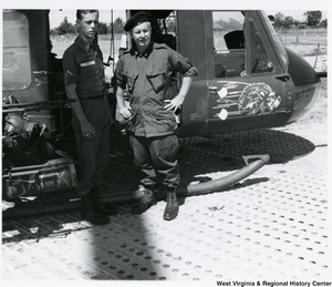 Congressman Arch A. Moore, Jr. standing beside a helicopter with PFC James Goff, (Shinnston, W.Va.). Goff was part of the chopper escort crew.