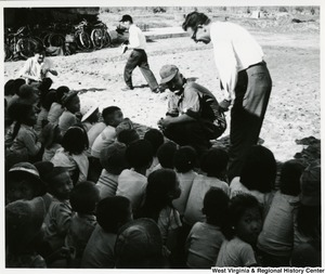 Congressman Arch A. Moore, Jr. crouched down in front of a group of children. Royall E. Norton, U.S. Regional Adviser, Region III, is standing beside Moore.