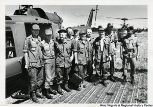 Congressman Arch A. Moore, Jr. (third from the left) standing beside a helicopter with a group of men.