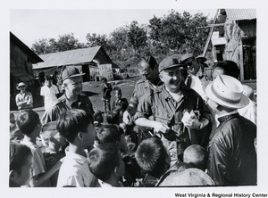 Congressman Arch A. Moore, Jr. and an unidentified group of men surrounded by children in Vietnam
