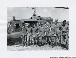 Congressman Arch A. Moore, Jr. standing beside a helicopter with a unidentified group of men in Vietnam.