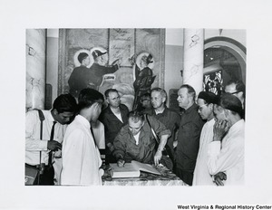 An unidentified man is signing the guest book at the Cai Dai temple in Tay Ninh, Vietnam. Congressman Arch A. Moore, Jr. is standing behind him.