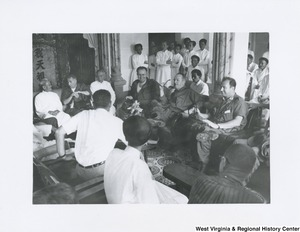 An unidentified group of men sitting and talking in Vietnam. Some men are standing in the background listening to the conversation.