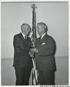 Congressman Arch A. Moore, Jr. shaking the hand of an unidentified man. They are also holding a trophy.