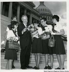 Congressman Arch A. Moore, Jr. standing on the steps of the Capitol with five Girl Scouts. Moore is looking into a basket one of the Girl Scouts is holding.