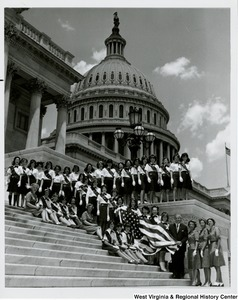 Congressman Arch A. Moore, Jr. standing on the steps of the Capitol with the Wheeling Girl Scout Troop. Moore is holding the American Flag with five Girl Scouts.