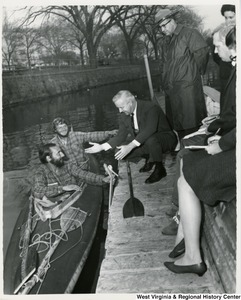 Congressman Arch A. Moore, Jr. is crouched down talking to two men in a kayak. Moore is holding out his hand. An officer is standing beside Congressman Moore.