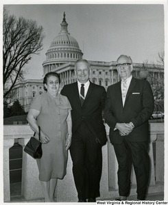 Congressman Arch A. Moore, Jr. (center) standing with an unidentified man and woman. The Capitol building can be seen in the background.