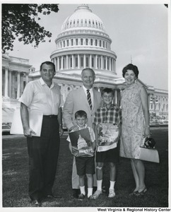 Congressman Arch A. Moore, Jr. standing on the Capitol lawn with Bob Gain's and his family. The two boys are holding the magazine, The Capitol.