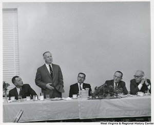 Congressman Arch A. Moore, Jr. giving a speech. He is standing at a table with four other men.