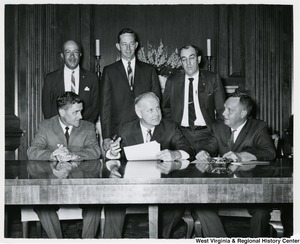Congressman Arch A. Moore, Jr. (seated, center) with five unidentified men, three of which are standing behind Moore. Moore is holding a sheet of paper.