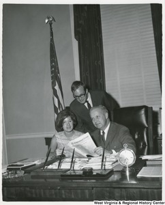 Congressman Arch A. Moore, Jr. at his desk with two of his interns.