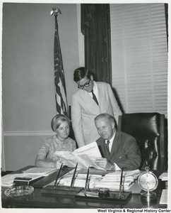 Congressman Arch A. Moore, Jr. seated at his desk showing two of his interns the Congressional Record.