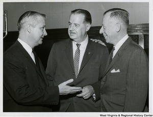 Congressman Arch A. Moore, Jr. speaking to Senator Hugh Scott (center) and an unidentified man.