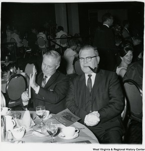 Congressman Arch A. Moore, Jr. sitting with an unidentified man at the 100 Years of Republican National Committee Celebration. Moore is holding a book.