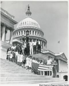 Congressman Arch A. Moore, Jr. standing on the steps of the Capitol with the seniors of Barrackville High School. Moore and six students are holding the American Flag.