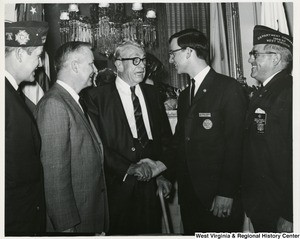 Richard A Robinson, Winner of the State Veterans of Foreign Wars annual Voice of Democracy contest shaking the hand of Senator Everett McKinley Dirksen. Left to right: Chester L. Shanklin, State Chairman of the contest from South Charleston, W.Va.; Congressman Arch A. Moore, Jr.; Senator Everett Dirksen; Richard Robinson from Fairmont, W.Va.; and State Department Commander Emmett Williams of Beckley.