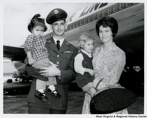 An unidentified couple holding two little girls. A plane is in the background.