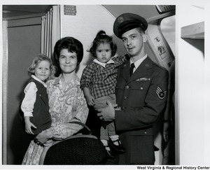 An unidentified couple holding two little girls on a plane.