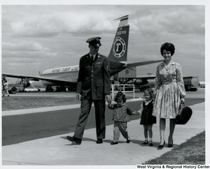 An unidentified family with two little girls, walking away from a airplane.