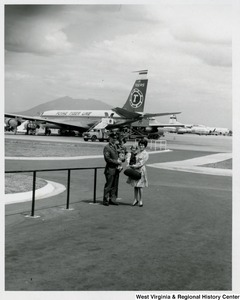 An unidentified family holding two little girls. A line of airplanes are in the background.