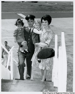 An unidentified family holding two little girls. They are walking up steps to a plane.
