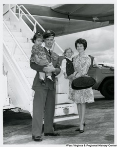 An unidentified family holding two little girls. They are standing in front of the steps to board a plane.