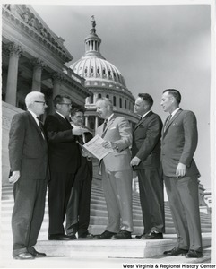 West Virginia mailmen asking Congressman Arch A. Moore, Jr. to help carry the mail on a legislative proposal to ease size and weight restrictions on parcel post packages. From left to right: Clyde Olver and Robert F. Glassgow of Wheeling; R.B. Smith of Wallace; Congressman Moore; Albert Moore and Walter W. Williams of Clarksburg.