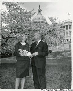 Congressman Arch A. Moore, Jr. standing with West Virginia's princess in the National Cherry Blossom Festival, Miss Carol Mimi Lee of Clarksburg. The Capitol building can be seen in the background.