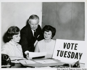 "Congressman Arch A. Moore, Jr., his wife, Shelley, and Lynn Moore looking over the sample ballot in his Clarksburg District Office. A sign on the table reads, ""Vote Tuesday."""
