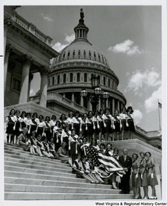 Congressman Arch A. Moore, Jr. on the steps of the Capitol with the Wheeling Girl Scout Troop. Moore is holding the American flag with five Girl Scouts.