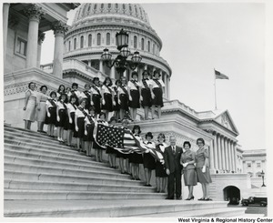 Congressman Arch A. Moore, Jr. on the steps of the Capitol with the Fairmont Girl Scout Troop 60. Six Girl Scouts are holding the American flag.