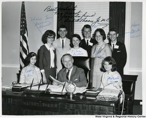 Grafton area students, who are in Washington D.C. for a regional 4-H Conference, stop to visit Congressman Arch A. Moore, Jr. Seated with the Congressman are Linda Dean (left) of Grafton and Marsha Jones (right) of Hepzibah. Standing from left are: Shirley Jean Hardman of Glenville, Dwight McDaniels of Grafton; Steven McWilliams of Webster; Kay Kunst of Grafton, and Harry Drake of Glenville. The photograph is signed by all the students.