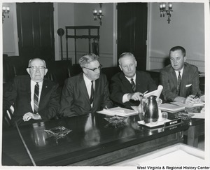 Congressman Arch A. Moore, Jr. pointing out an important fact to the Reverend Mr. Arthur Prichard of Mannington at a hearing in Washington on the Upper Buffalo Creek Watershed Project.  With Mr Prichard for the hearing was L.E. Moore (left), of Mannington, and Marion County Commissioner John Obondko on the right.  The hearing was held by the Subcommittee on Conservation and Credit of the House of Agriculture Committee.
