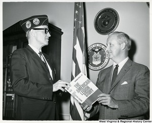 "Herald Stringer, National Legislative Director of the American Legion (left), presenting a copy of ""The American Legion Story"" to Congressman Arch A. Moore, Jr."