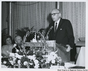 An unidentified man is speaking at the Italian Sons and Daughters banquet in Weirton, W.Va. Congressman Arch A. Moore, Jr. and his wife, Shelley, are seated to the left of the speaker.