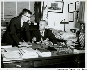 Congressman Arch A. Moore, Jr. seated at his desk talking to an unidentified man. The man appears to be taking notes.