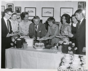 Congressman Arch A. Moore, Jr. placing a piece of cake on a plate held by an unidentified woman.