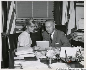 Congressman Arch A. Moore, Jr. having a conversation with an unidentified woman. They are both seated at Moore's desk.