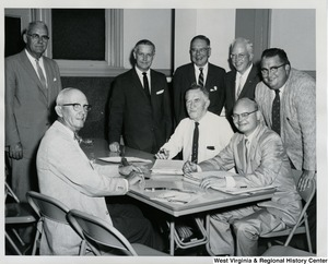 Congressman Arch A. Moore, Jr. (standing, fourth from the right) with an unidentified group of men going over some documents.
